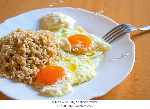 Two fried eggs with rice and alioli sauce. Close view