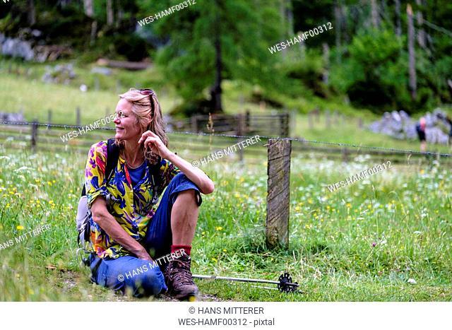Female hiker sitting on meadow