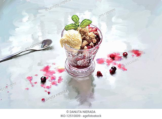 Redcurrant fruit crumble with scoop of ice cream in glass bowl