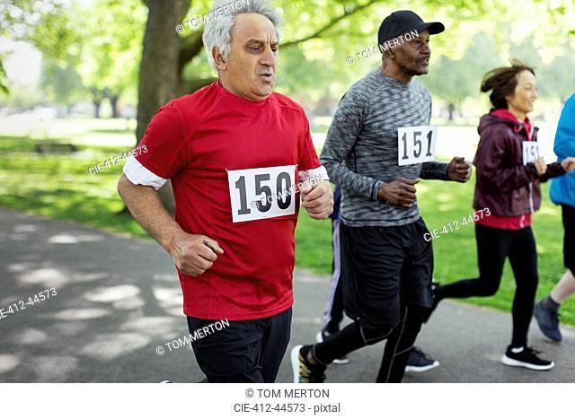 Active senior man running sports race in park