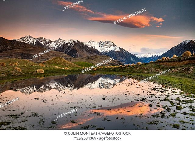 Dawn lights up peaks in Reishek Mountains, reflection in small pond, Rakaia, Valley, Canterbury, New Zealand