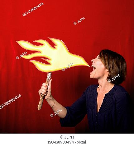 Woman holding cardboard cut-out of flames pretending to breathe fire