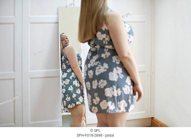 Young woman looking at reflection in mirror