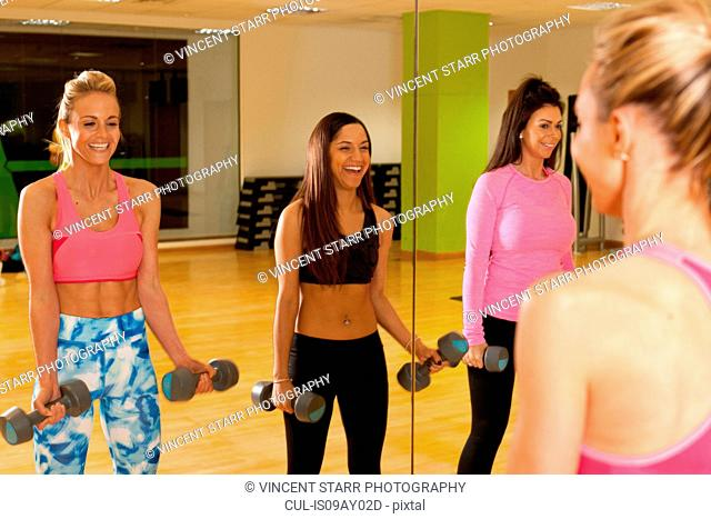 Mirror image of women in gym using dumbbells