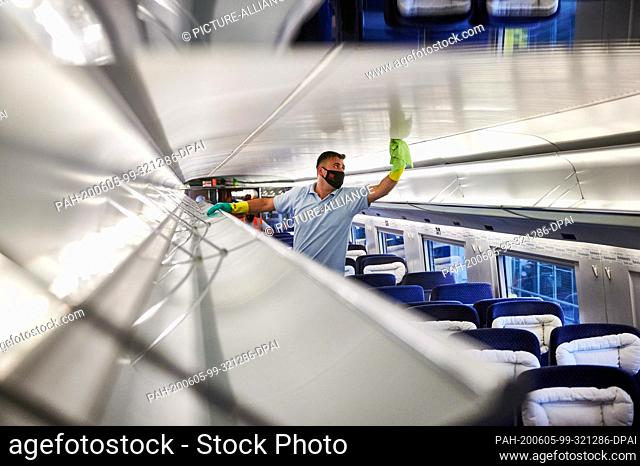 05 June 2020, North Rhine-Westphalia, Dortmund: An employee of DB-Fernverkehrswerk Dortmund cleans luggage racks in an ICE with face masks and rubber gloves
