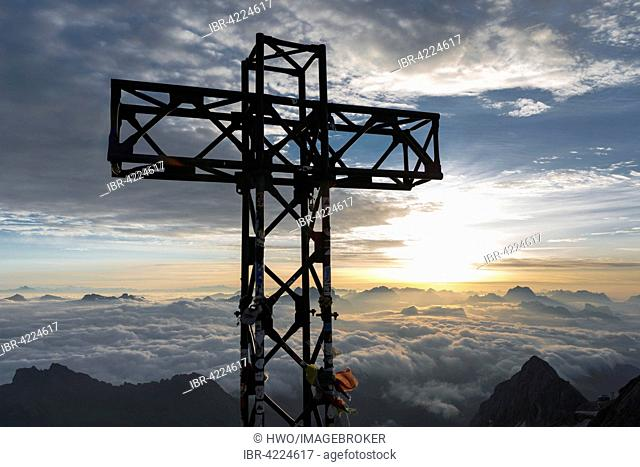 Sunrise at the summit cross of Punta Penia, overlooking the cloud cover, Marmolada, highest point in the Dolomites, Alps, South Tyrol, Trentino