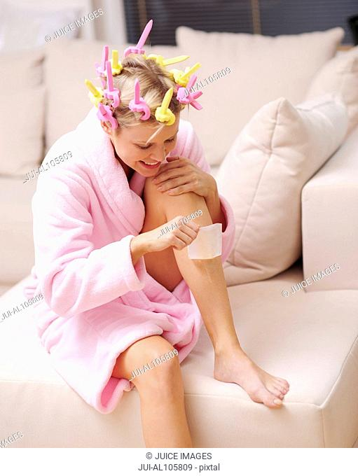 Young woman with curlers in hair waxing her legs