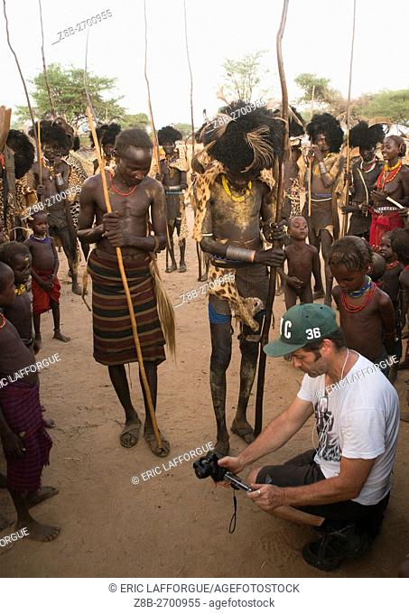 Ethiopia, Omo Valley, Omorate, european tourist showing the screen of his camera in dassanech tribe