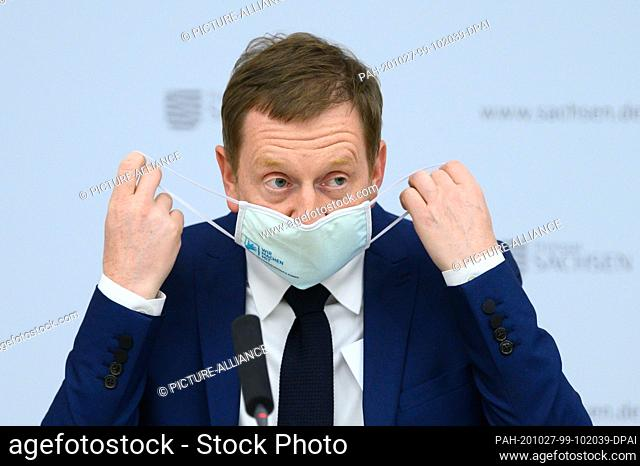 27 October 2020, Saxony, Dresden: Michael Kretschmer (CDU), Prime Minister of Saxony, takes off his mouth and nose protector at the beginning of a press...