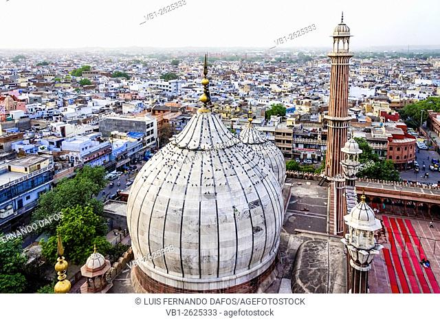 Aerial overview of Old Delhi from minaret of Jamaa Masjid mosque with minaret and domes in foreground. Delhi, India