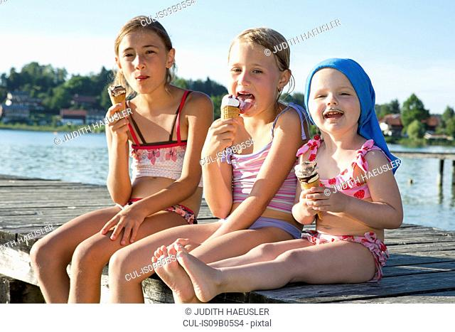Two sisters and female toddler on pier eating ice cream cones, Lake Seeoner See, Bavaria, Germany