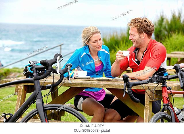 Cyclists relaxing at picnic table overlooking ocean