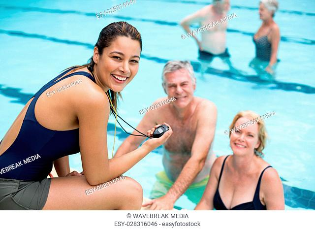 Young female trainer and senior swimmers at poolside