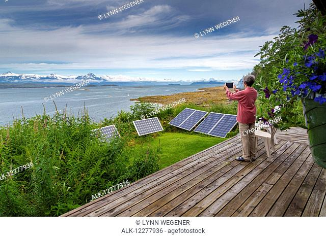 A woman takes a photo of the Chilkat Mountain Range with solar panels in the foreground, Southeast Alaska, Summer