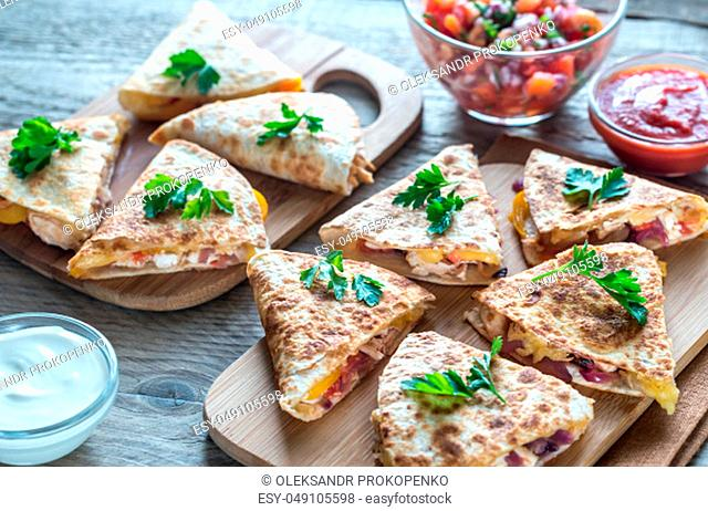 Quesadillas with cheese, spicy chicken and vegetables with different sauces