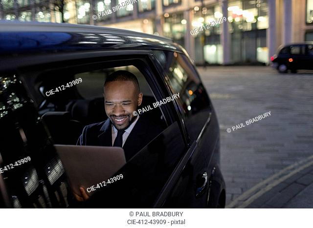 Smiling businessman using laptop in crowdsourced taxi at night