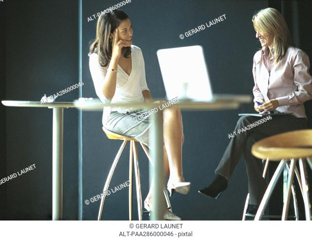 Businesswomen sitting and talking in cafe setting