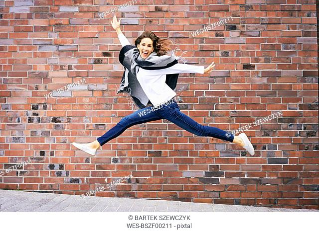 Happy young woman jumping in the air in front of brick wall
