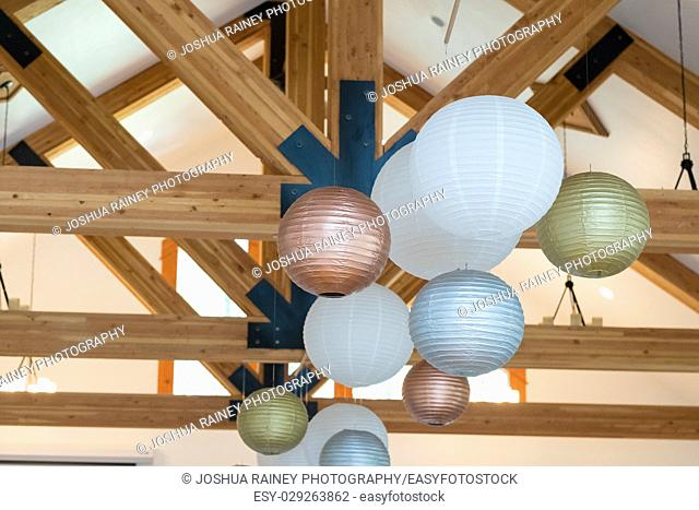 Wedding reception decor of white, gold, and silver paper lanterns hung high in the rafters at a wedding venue