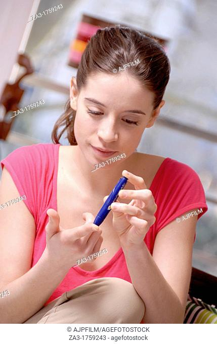 Blood glucose testing  Young diabetic woman testing her blood