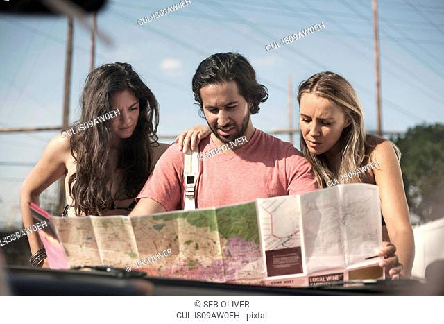 Windscreen view of three young adult friends reading roadmap, Los Angeles, California, USA