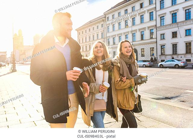 Young man and female friends strolling with takeaway coffee on city street