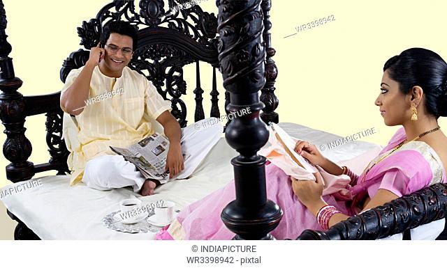 Bengali woman stitching while husband talks on a mobile phone