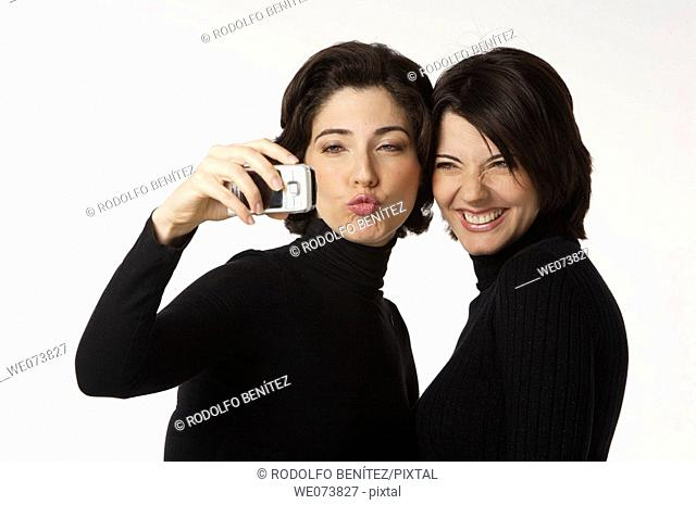 Twin sisters having their picture taken with a cell phone. One smiling, the other one blowing a kiss