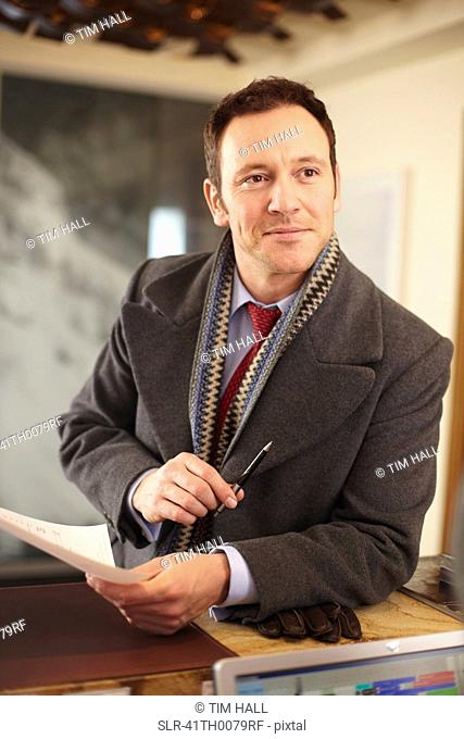 Businessman with paper at front desk