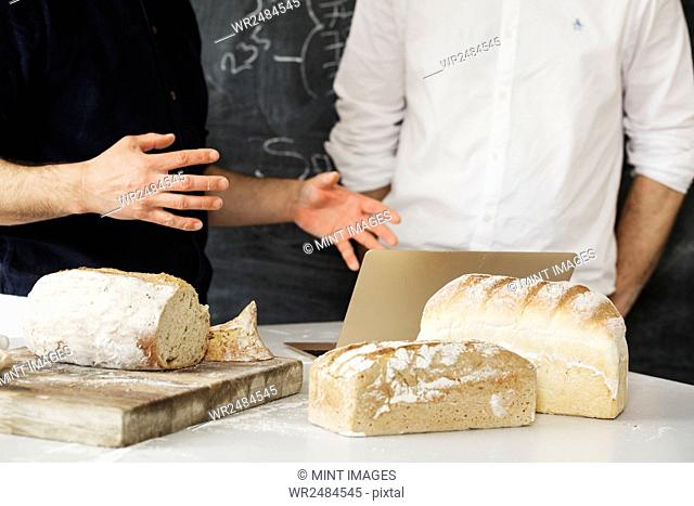 Close up of two bakers standing at a table, using a laptop computer, freshly baked bread