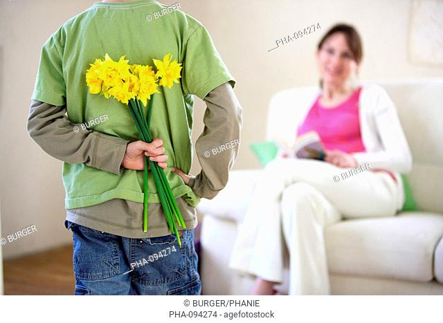 8 years old child gives his mother a bunch of daffodils