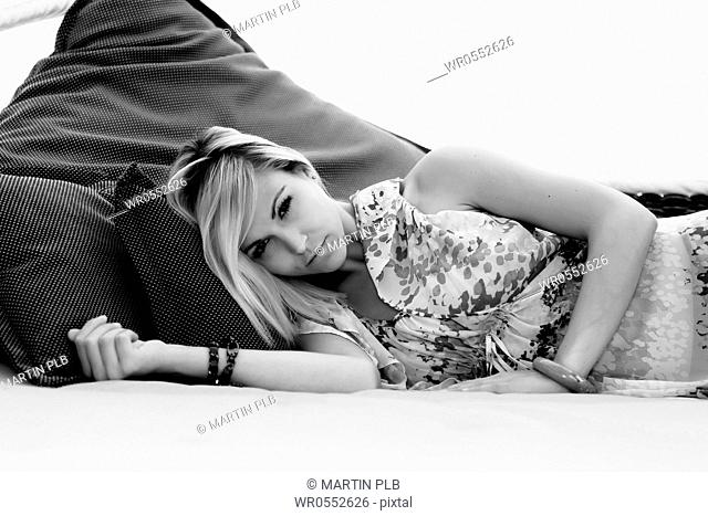 beautiful young woman relaxing in garden lounge
