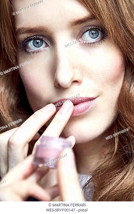 Portrait of redheaded woman applying cream on her lips