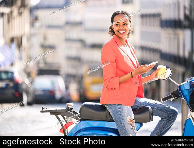 Smiling young woman with motor scooter and cell phone in the city, Lisbon, Portugal