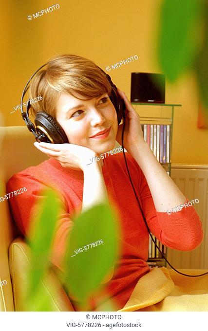 Eine junge Frau hoert Musik ueber Kopfhoerer, 2005 - Germany, 17/07/2005