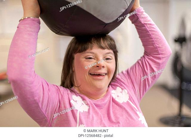 Woman with Down Syndrome working out with an exercise ball