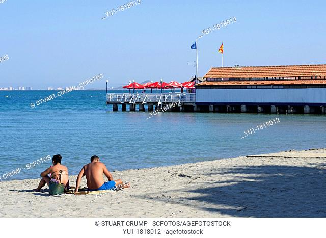 Couple of the beach beside a Traditional Spanish Restaurant Set on a wooden pier over the Mar Menor Sea at Los Alcazares Murcia Costa Calida, Spain