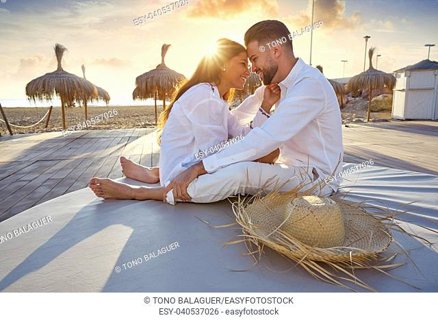 Couple young in love hug on the beach vacation sunrise at Spain