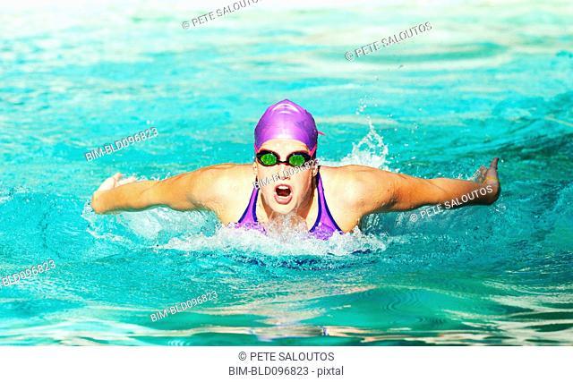 Caucasian teenager swimming in swimming pool