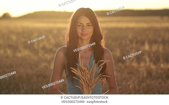 Lovely girl holding ripened wheat ears on field