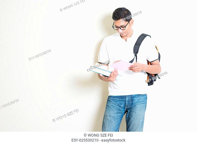 Portrait of adult Indian university student with bag reading book. Asian man standing on plain background with shadow and copy space