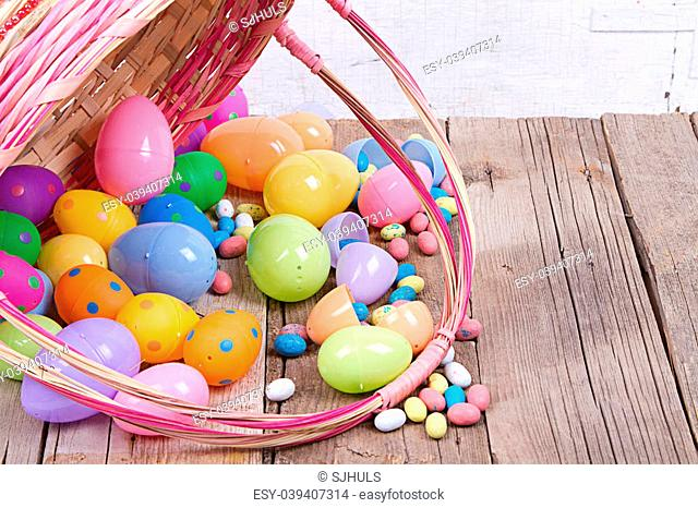 Plastic easter eggs by nest filled with candy in a Easter basket on a wooden background