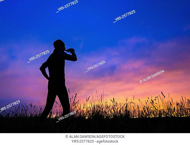 Monday 7th September 2015, Cowpen Bewley Woodland Park, Billingham, north east England. Weather: Jogger on hill in woodland park silhouetted against glow from...