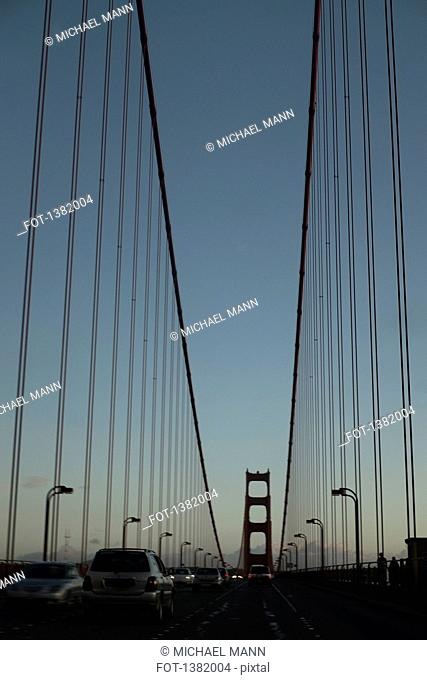 Cars on Golden Gate Bridge against clear sky during dusk