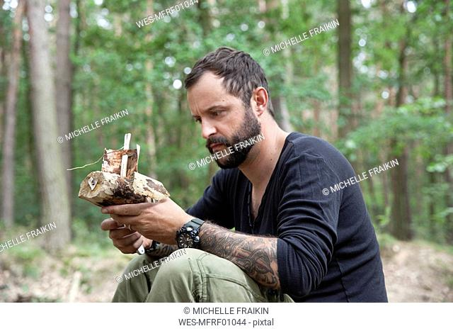 Man looking at carved wooden boat in the forest