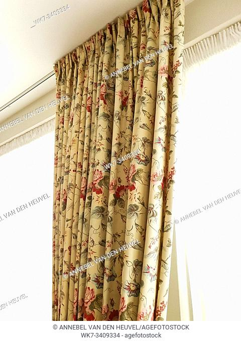Vintage beige curtains hanging on window with colorful pattern in a light room beauty