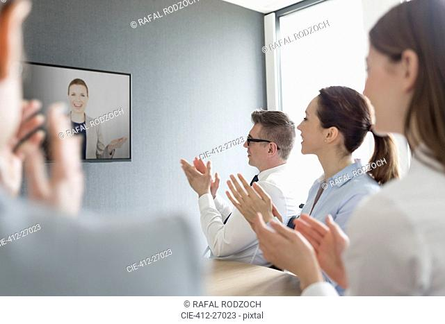 Business people clapping for businesswoman on video conference screen