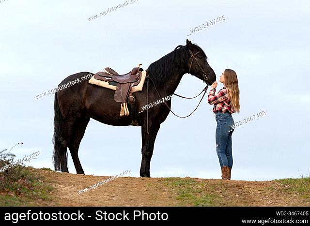 Side view of a blonde teenager cowgirl in front of her black horse with the saddle