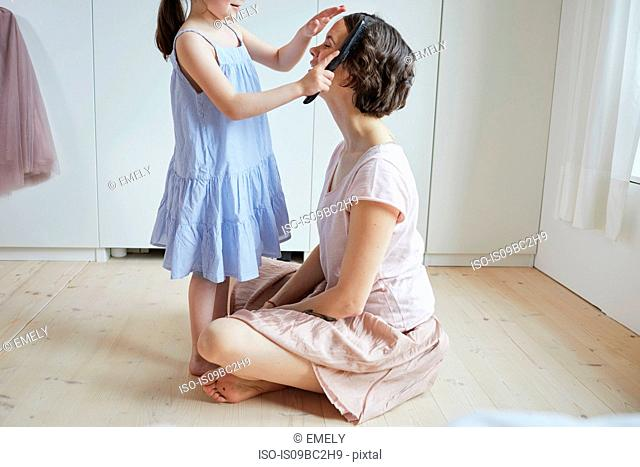 Mother sitting on floor, daughter brushing mother's hair, mid section