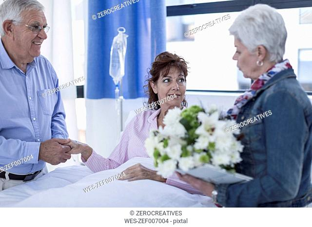 Senior couple visiting mature patient in hospital